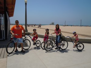 Family bike ride on CA beach